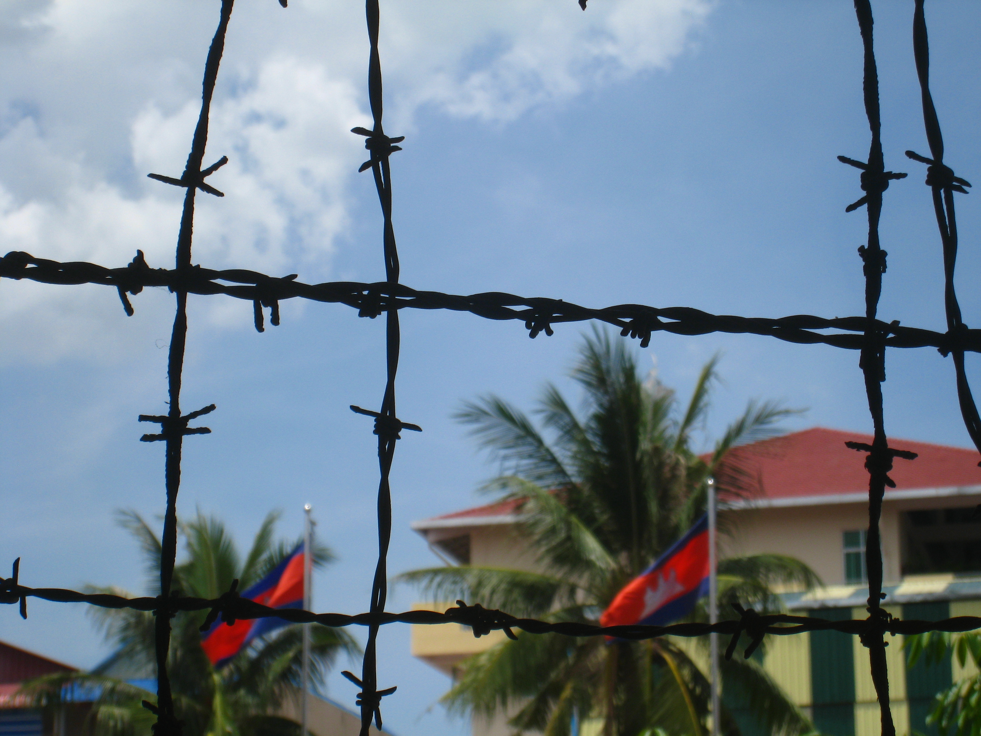 Barbed wire hides the Cambodian flag
